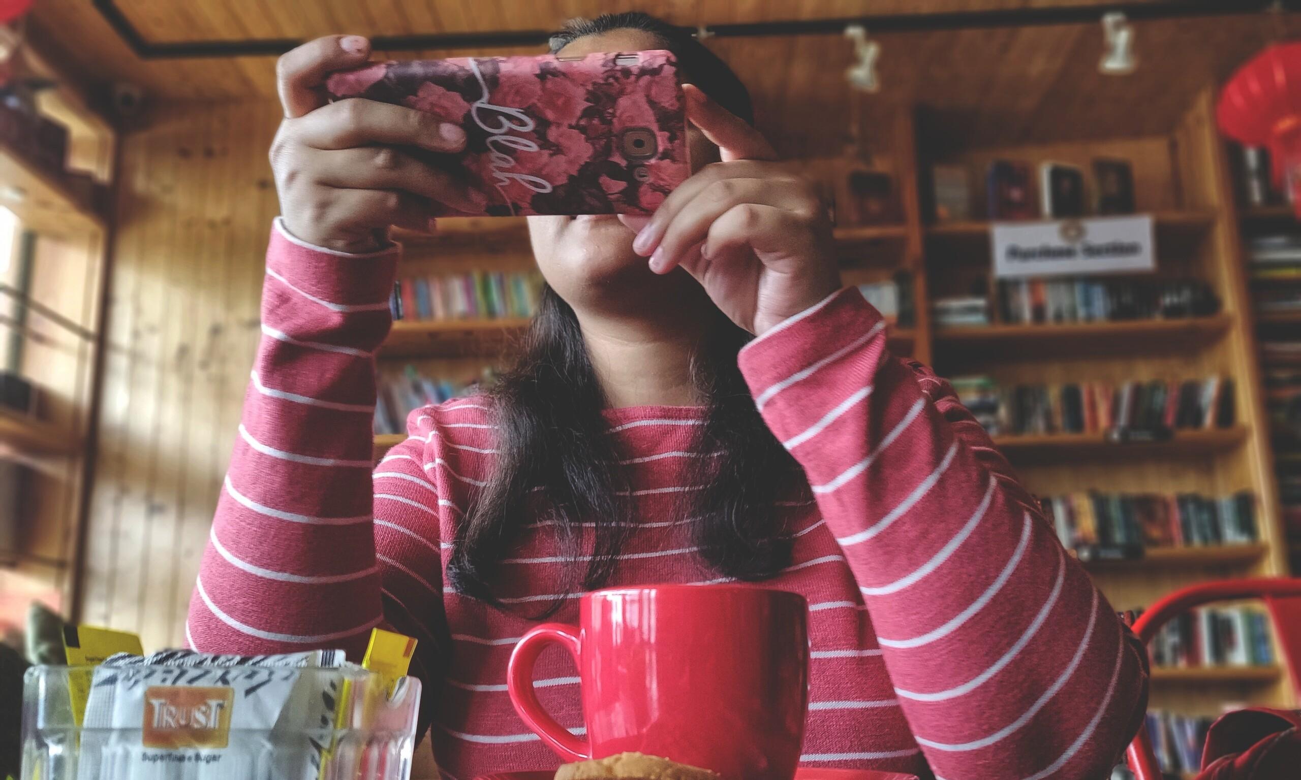 Frau fotografiert mit Smartphone.